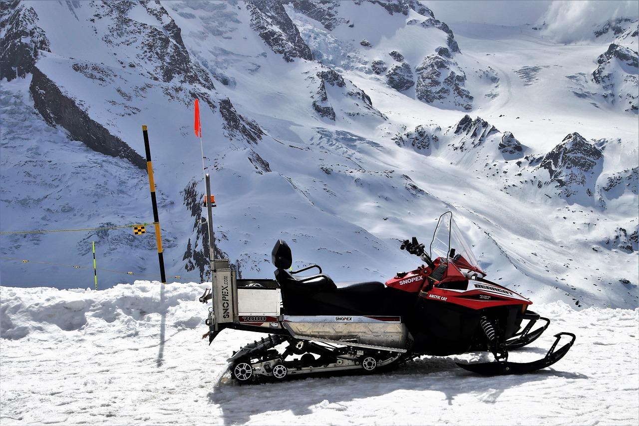 Röd skoter i snöig terräng